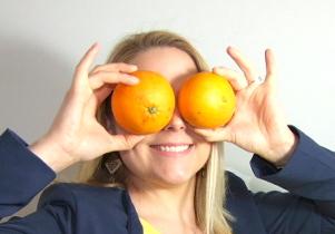 dieteticienne blonde, souriante, portant deux oranges devant ses yeux